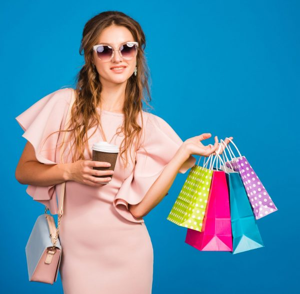 young stylish sexy woman in pink luxury dress, summer fashion trend, chic style, sunglasses, blue studio background, shopping, holding paper bags, drinking coffee, shopaholic